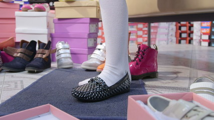 Little girl trying on loafers in children shoe store