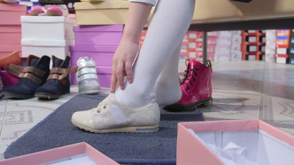 Child trying on new shoes for junior girls in shoe store