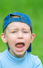 Little boy in denim cap indulges, pretending that she was crying