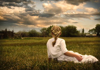 Girl wearing a dress sitting in a pasture
