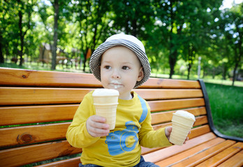 a little boy holding two ice creams