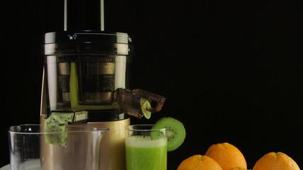 squeezed fruit juice orange kiwi using masticating juicer