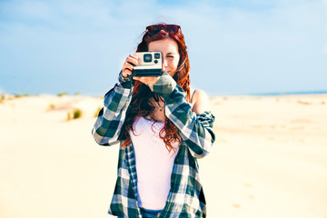 Woman with vintage photo camera instant