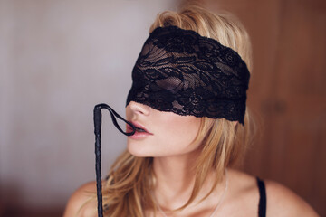 Sexy woman in lace eye cover bite whip