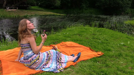 woman drink cider champagne alcohol sitting on plaid near river