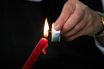 Mano di uomo che accende una candela rossa