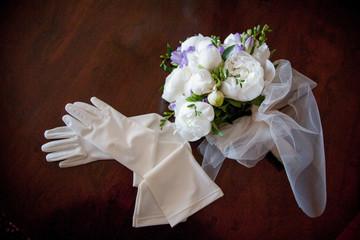 Guanti della sposa e bouquet di nozze su sfondo scuro