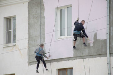 Промышленные альпинисты красят здание.