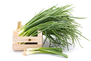 Fresh spring onions in wooden crate