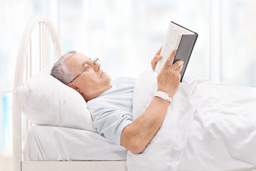 Mature patient lying in bed and reading a book