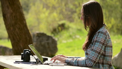 Beautiful girl using a laptop at the park