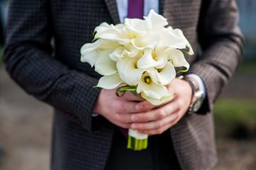 bouquet in hands of the groom