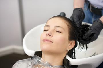 Beautiful woman washing hair in hair studio