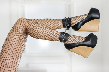 Cuffed legs in fishnet stockings extreme platform shoes