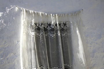 White lace curtain on a rustic white wall.