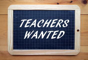 The phrase Teachers Wanted on a slate board