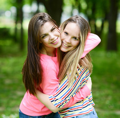 Two young girl friends in a hug at park