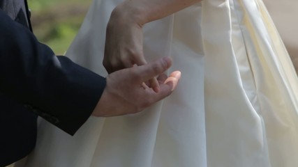 Gently connected hands of a newly-married couple with wedding
