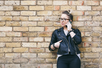 Hipster woman talking on smart phone in London.