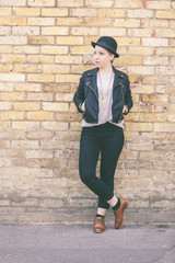 Hipster woman portrait against a brick wall in London.