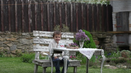Cute little boy, sitting on an old bench in a garden