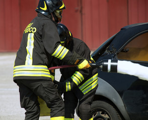 two firemen in action with foam to put out the fire of the car