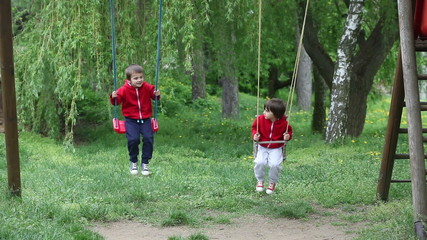 Two adorable boys, swinging on the playground together