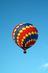 hot air balloon of primary colors flying in sky