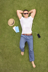 Casual young man lying in field and listening to music