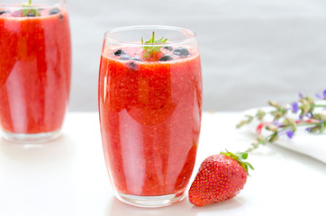 Two glasses of fresh berries fruit and smoothies on white . Blue