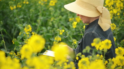 Female Farmer with Digital Tablet in Oilseed Rapeseed Field