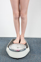 The feet of a girl standing on a bathroom scale