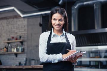 Charming female waiter in apron writing order