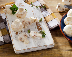 Fresh white mushrooms  on  a white wooden cutting board.
