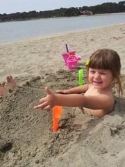 bambina gioca in spiaggia con la sabbia