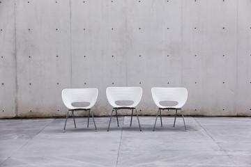 Sillas blancas en fondo de concreto