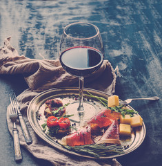 Wine appetizer set. Glass of red wine, vintage dinnerware