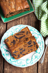 Cake with prunes and almond flour on a wooden table with a green