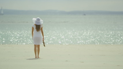 Young woman strolls onto the beach