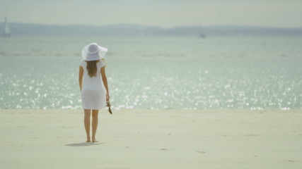 Young woman in a dress walks along the beach enjoying the view