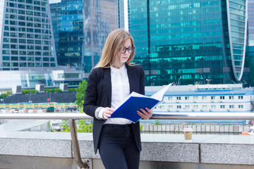 Woman reading documents folder on a background of skyscrapers