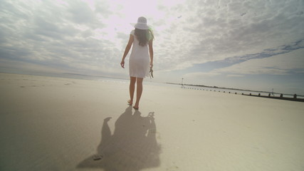 Woman walks on the beach on a nice day in slow motion