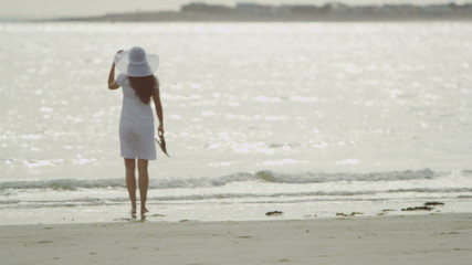 Young woman walks along the beach shore in slow motion