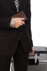 Business traveling pulling suitcase and holding passport
