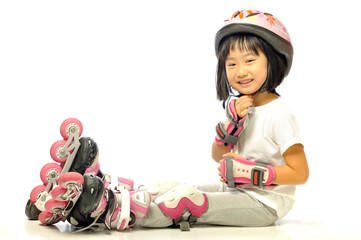Asian smiling little girl is wearing roller blades