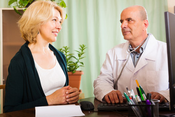 Mature male doctor talking with aged female patient