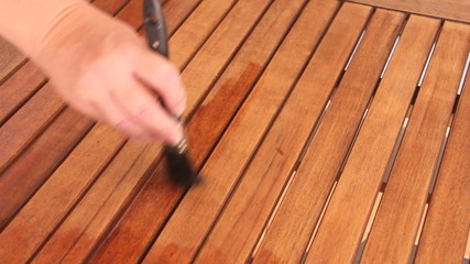 Person painting a wooden table with varnish