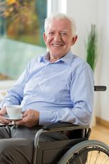 Happy man on wheelchair drinking coffee