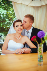Bride and groom posing at the decorated banquet table in the