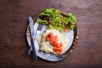 Scrambled egg and smoked salmon on wooden